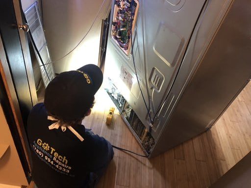 Dennis Repairing Fridge in Calgary
